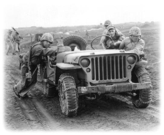Jeep_with_guys_pushing_it_up_a_hill